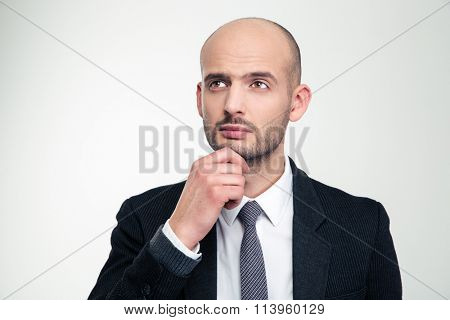 Portrait of thoughtful attractive young business man in black suit over white background