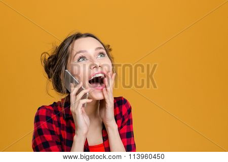Charming surprised content young woman in plaid shirt talking on cell phone over yellow background