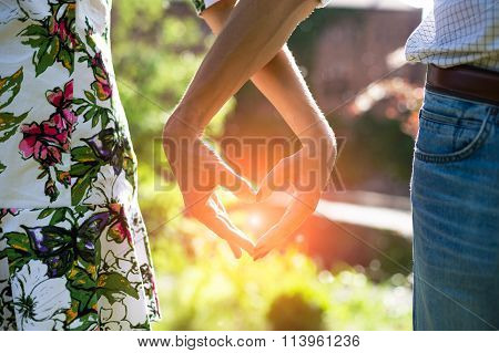 Young couple in love holding hands on the sunset during summer evening