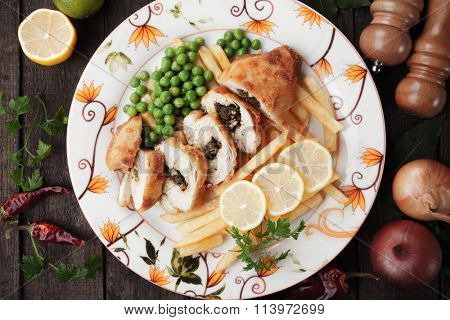 Chicken kiev served with french fries and green peas