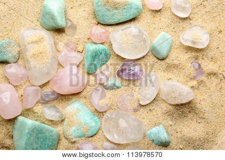 Semiprecious stones on sand background