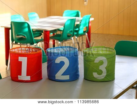 Cans With Large Numbers On The Desk In The Classroom