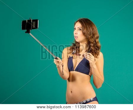 Happy young woman in blue bikini swimsuit taking selfie with smatphone on green background