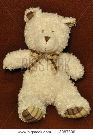 Teddy bear sits on fetr fabric