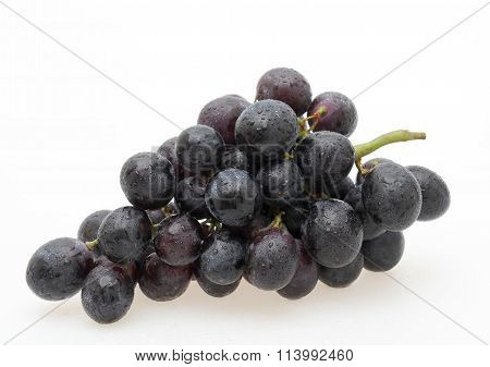 A bunch of ripe red grapes isolated on white
