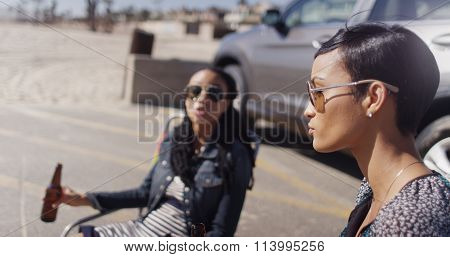 Two African American Women Sitting In Beach Chairs Having A Drink And Talking