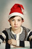 funny close up portrait of a preteen boy in santa hat representing chrisrmas elf with grimace and protruding ears poster