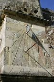 Wimborne Minster sundial in Dorset. An unusual sundial with three sides so the time can be told across the year. The other two gnomons are just visible to either side. It stands separately from the building. Background of blue sky and tower. poster