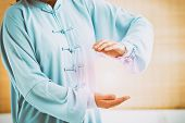Beautiful woman doing qi gong tai chi exercise or reiki wearing professional, original Chinese clothes at gym poster