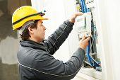 Electrician installing energy saving meter poster