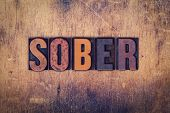 """The word """"Sober"""" written in dirty vintage letterpress type on a aged wooden background. poster"""