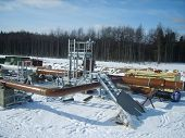 Platform of construction of pipelines. Booster pump station. Snow-covered area of the pipeline. poster