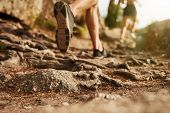 Cross country running. Closeup of male feet run through rocky terrain. Focus on shoes. poster