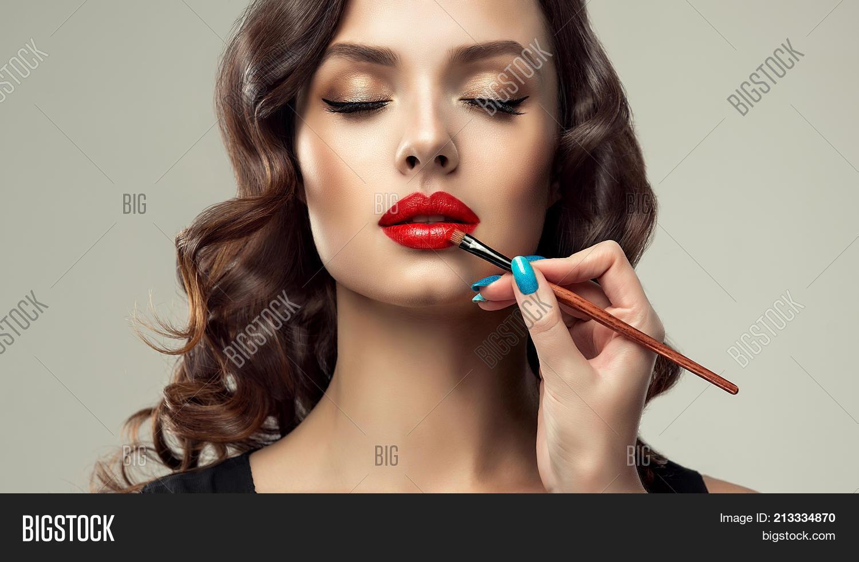 Makeup artist applies red lipstick on lips . Beautiful woman face. Make up detail.