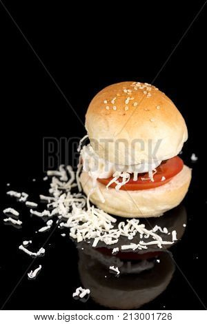 Meatball In A Bun With Tomato Mayonnaise And Grated Cheese On The Black Background