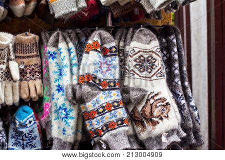 Products made of yarn knitted socks showcase with knitted socks on the market. Knitted gloves and socks with colorful ornaments for sale on the market