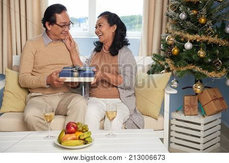 Elderly woman giving present to her beloved husband