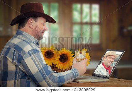 Two friends chat online and drink whiskey at the same time. One cowboy wearing brown hat and plaid shirt sits at wooden kitchen with sunflowers and looking at laptop screen. His friend is seen on monitor. Both hold whiskey glasses