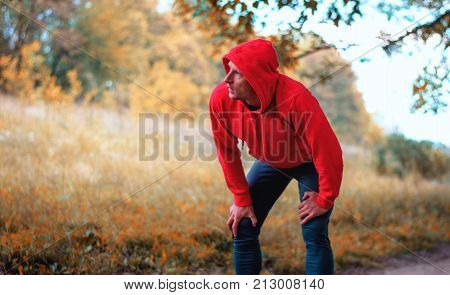 A Young Jogger Man Rest After Running On A Bright Yellow Autumnall Background.