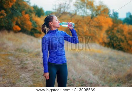 A Slim Caucasian Jogger Woman Idrink Water From The Bottle After Jogging.
