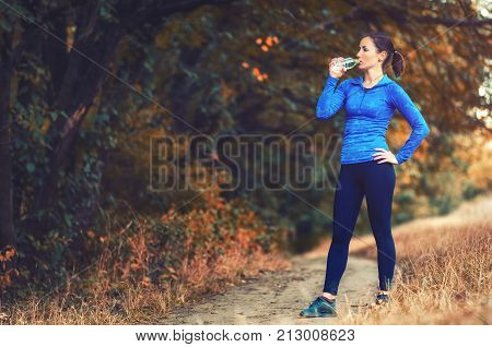 A Young Athletic Jogger Woman I Drink Water From The Bottle After Jogging On A Colorful Autumnall Fo