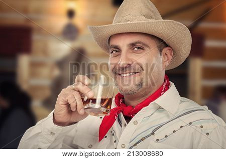40 years old cowboy in beige hat and red scarf drinks neat scotch whiskey in bar and man is enjoying it
