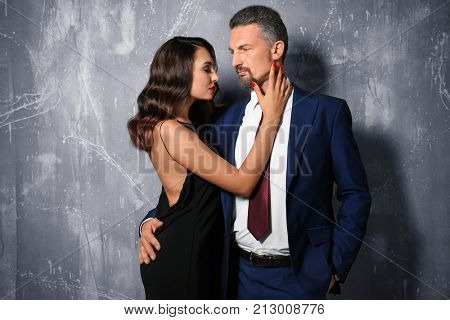Attractive couple in formal wear on grey background