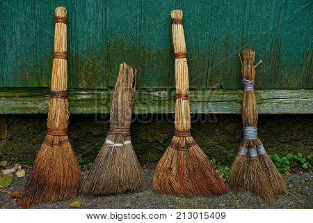 a set of old brooms stand at the green wooden wall
