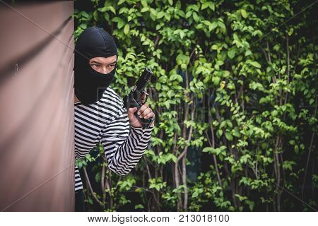 Robber hiding behind the wall looking at victims and waiting to come nearest for stealing the valuables.