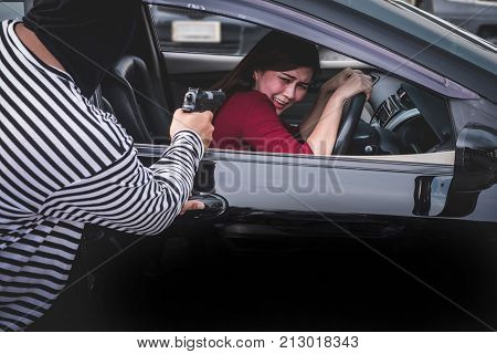 Robber pointing a gun to scare young woman and try to rob her car.