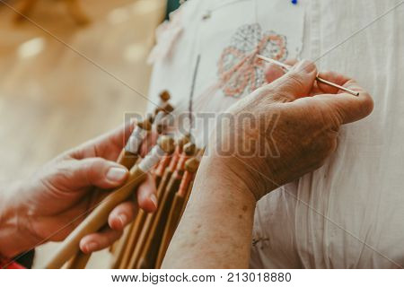 Close-up of woman hands works with bobbin lace, hand made crafting Laces, toned