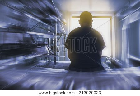 Man sitting on the hospital bed looking through the window concept of dying patient.