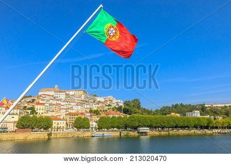 Panoramic view of old Coimbra city and Mondego river from Santa Clara bridge with flag of Portugal flying on foreground.Coimbra is famous for its University, founded in 1290, among the first in Europe