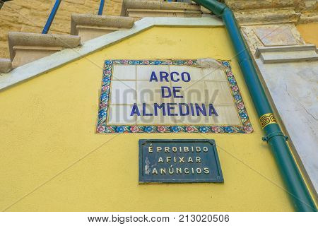 Coimbra, Portugal - August 14, 2017: close up of popular landmark of Arco de Almedina or Arch of Almedina, the iconic Archway in medieval town of Coimbra. Wall background.