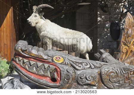 Sochi, Hosta District, Krasnodar region, Russia - July 14, 2016: Sculptural composition of a stuffed goat and carved wooden crocodile at the foot of the tower on a mountain Big Ahun, Sochi