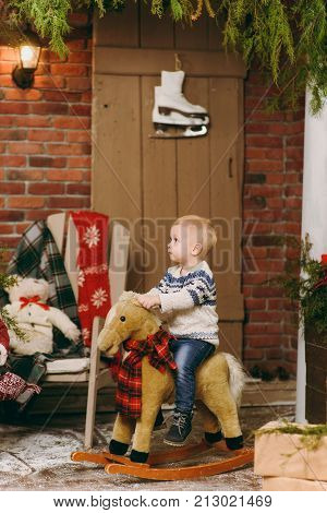 Playful Smiling Happy Cute Little Child Boy Dressed In Sweater And Jeans Sitting On Rocking Horse In