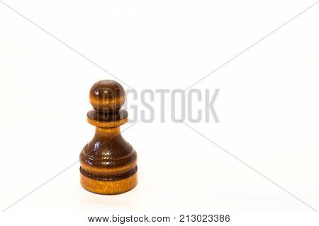 The black chess pawn of wood on the white background