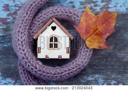 toy house is wrapped in a warm scarf with an autumn leaf. The concept is warm cozy loving protecting the house. We prepare the house for the cold.