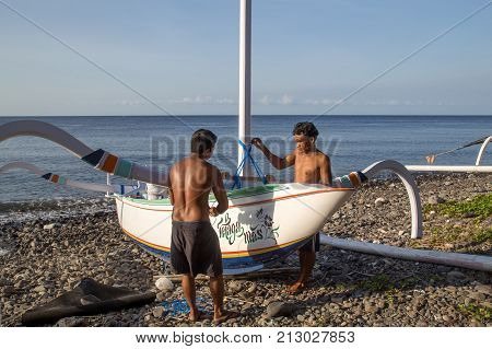 Bali, Indonesia - July 06, 2015: Two fishermen preparing their traditional fishing boats on a beach close to Amed