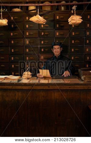 Portrait of traditional Asian medicine practitioner in apothecary