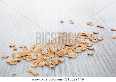 Pile of oat flour with oat flakes on wooden table. Celiac flour alternative. Oat flour.