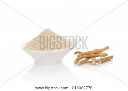 Ashwagandha powder in spoon with roots. Isolated on white. Superfood remedy .