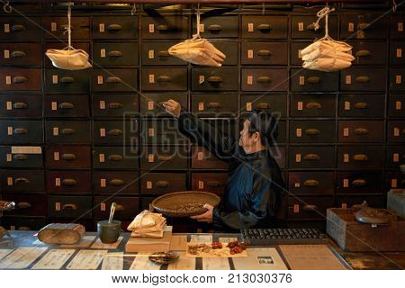 Apothecary worker opening drawer to take out main ingredient