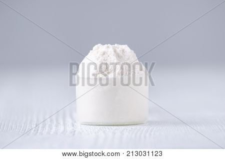 a scoop with white powder on gray background, selective focus