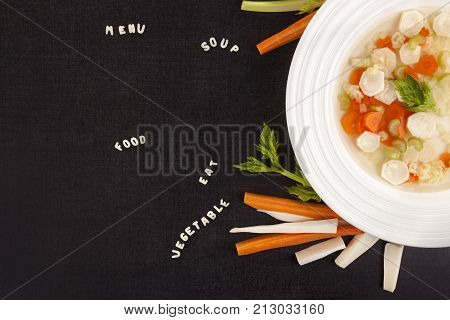 Healthy vegetable soup with alphabet noodles from above. ABC pasta letters. Lunch menu. Vegetable broth bouillon.