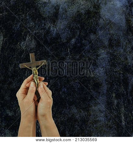 Praise the Lord Background - Female hands holding a small statue of Christ on the Cross, against a shiny black stone effect background with copy space above and to the right
