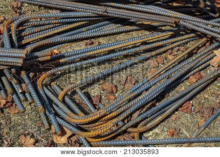 Bundles of bent and rusted steel rebar at a construction site, horizontal aspect