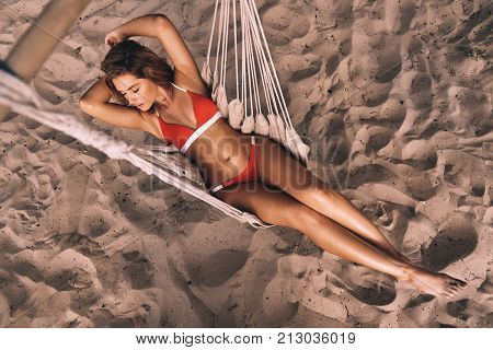 Summer relaxation. Full length top view of attractive young woman in swimwear keeping hands behind head while lying down in hammock outdoors