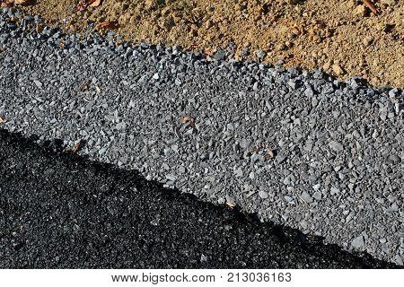Diagonal View Of Layers Of Roadway With Asphalt, Gravel, And Dirt, Horizontal Aspect