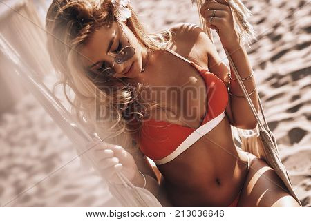 Irresistible beauty. Top view of attractive young woman in red bikini enjoying summer day while sitting in hammock on the beach